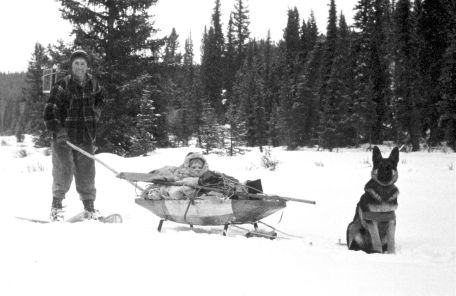 Park Warden Toni Klettl on the North Boundary with his daughter, Linda, and dog, Storm (pulling Linda in the home-made sled) in winter, late 1950s.