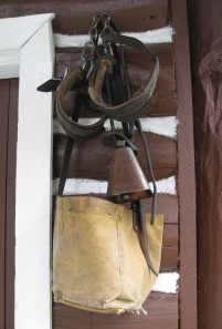 A pair of hobbles, a bell, and an oat bag hang on tacks outside a warden cabin.
