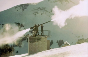 Toni Klettl and Denny Welsh trigger controlled avalanches on the slopes above Marmot Basin Ski Area with a 105 mm recoilless rifle. The concussive force of the backblast, a powerful discharge of hot air and gases, is visible at the rear of the rifle.