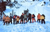 It is not uncommon for skiers venturing into closed areas or on slopes off the beaten path to trigger avalanches. Here, park wardens and volunteers search for a skier buried by an avalanche by probing with metal rods.
