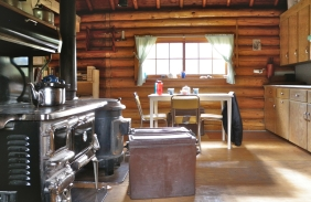 The interior of Brazeau warden cabin, the district headquarters cabin of the Brazeau District. Note both the cook stove and the heater stove behind it.